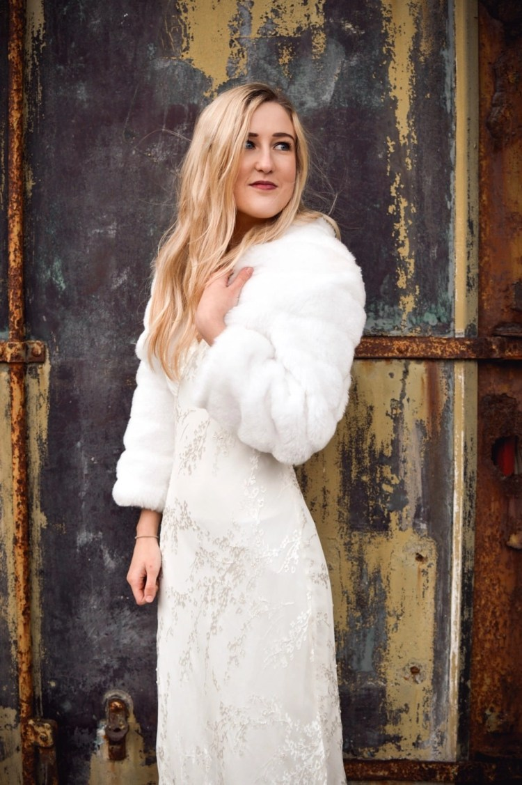 BB42 – faux fur cropped bridal jacket with sleeves on blonde bride with hair down in front of rusty door