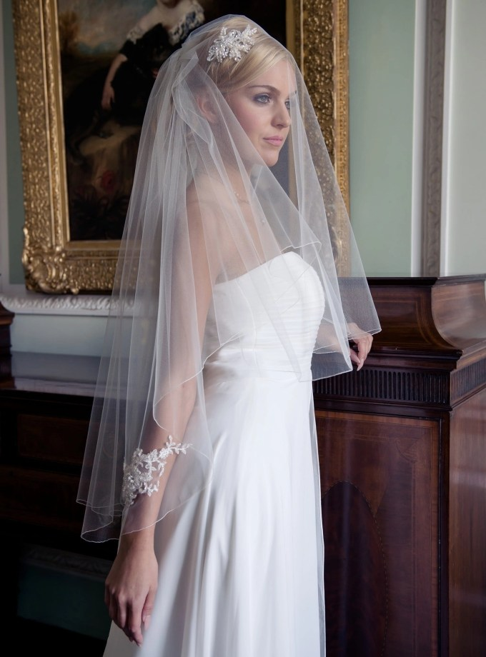 Bride in grand stately home wearing a wedding veil with lace appliques
