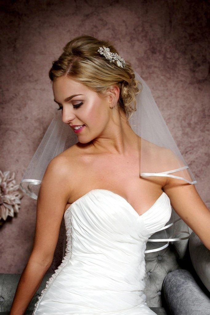 Close up of bride wearing pretty elbow length ribbon edge veil