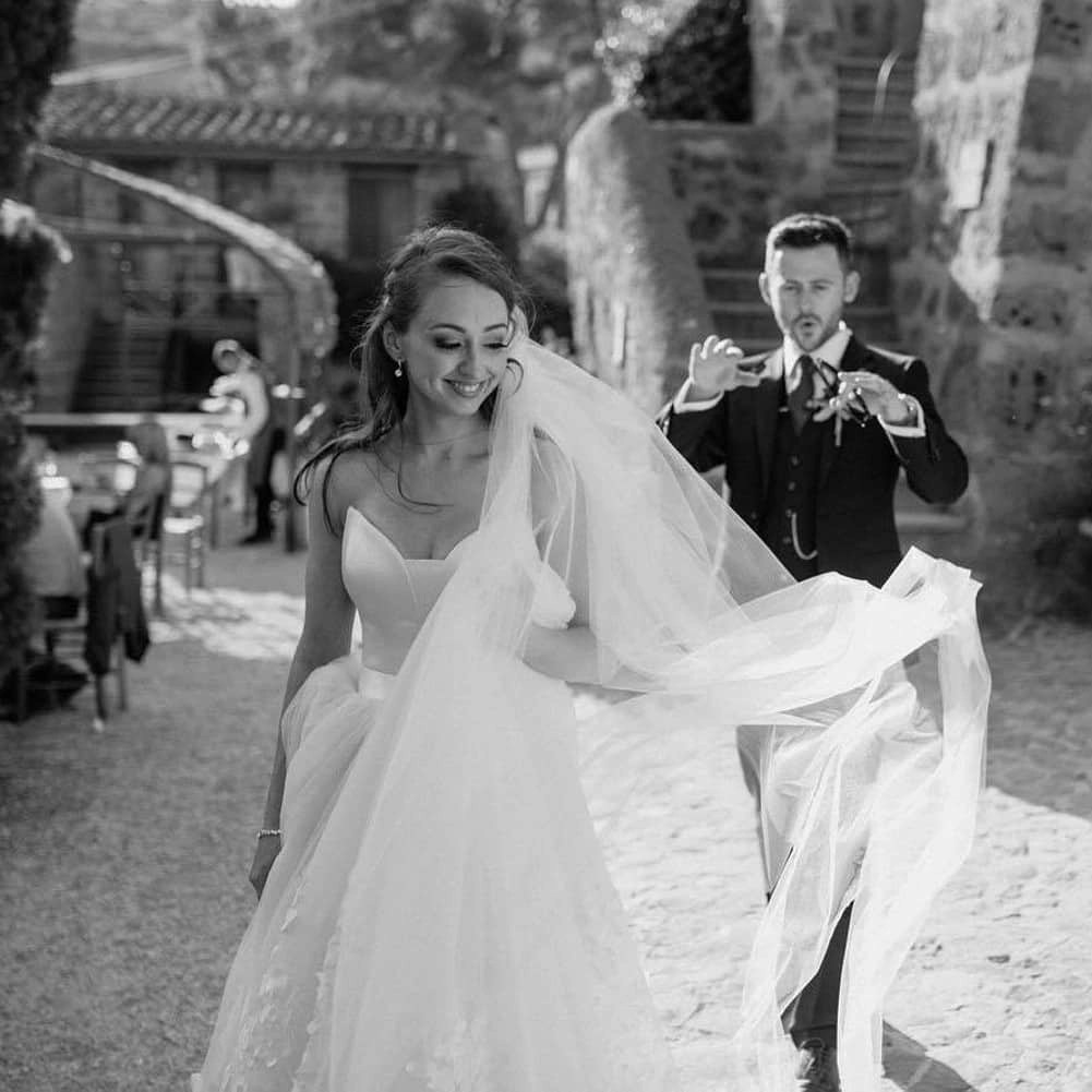 Long flowing chapel length veil caught in the breeze on real bride Emma