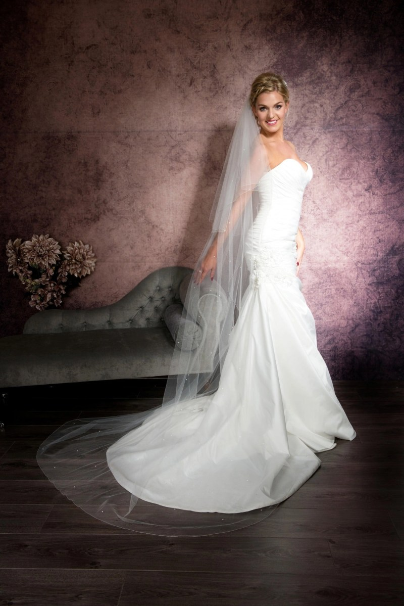 Smiling bride wearing a long floaty chapel length veil with scattered diamantes