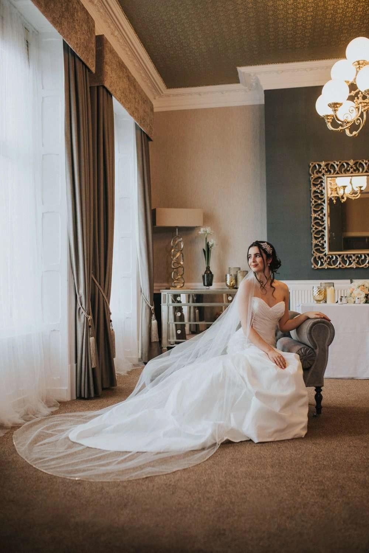Natalia – one layer chapel length veil with a rhinestone trim on model bride