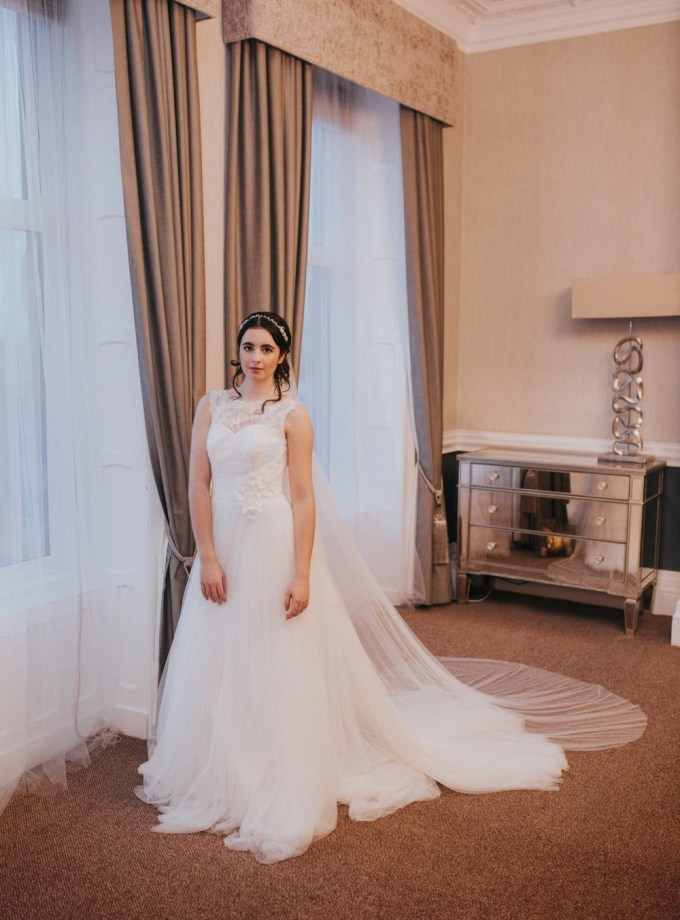 Bride wearing long two tier silk effect veil over the face - pretty drop veil with pearls