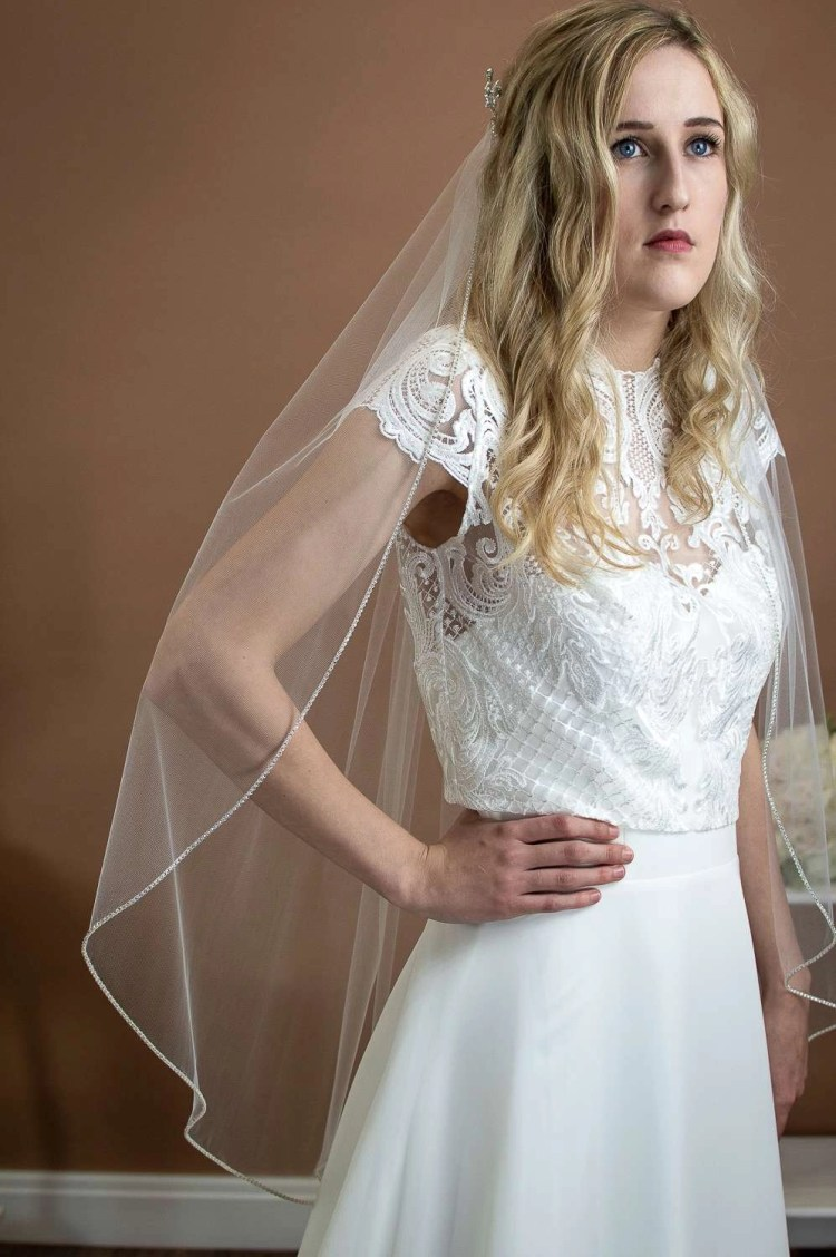 Sophia - single layer hip length veil with a sparkly rhinestone edge on a bride front view closeup