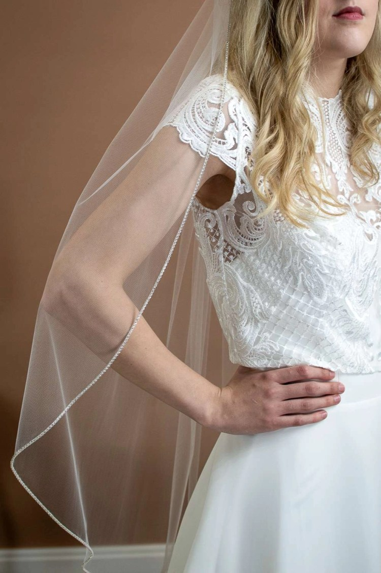 Sophia - single layer hip length veil with a sparkly rhinestone edge on a bride side view closeup
