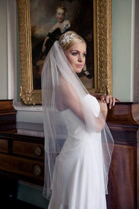 Bride in stately room wearing fingertip length veil with crystals & pearls