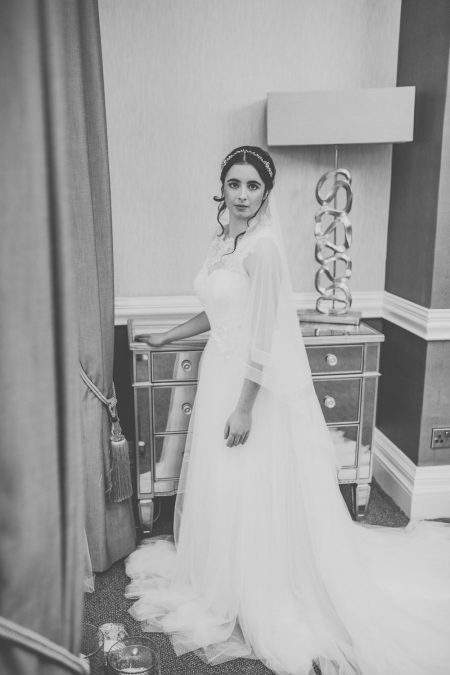 Pretty bride wearing a two tier fingertip length veil with a sheer ribbon edge in black and white