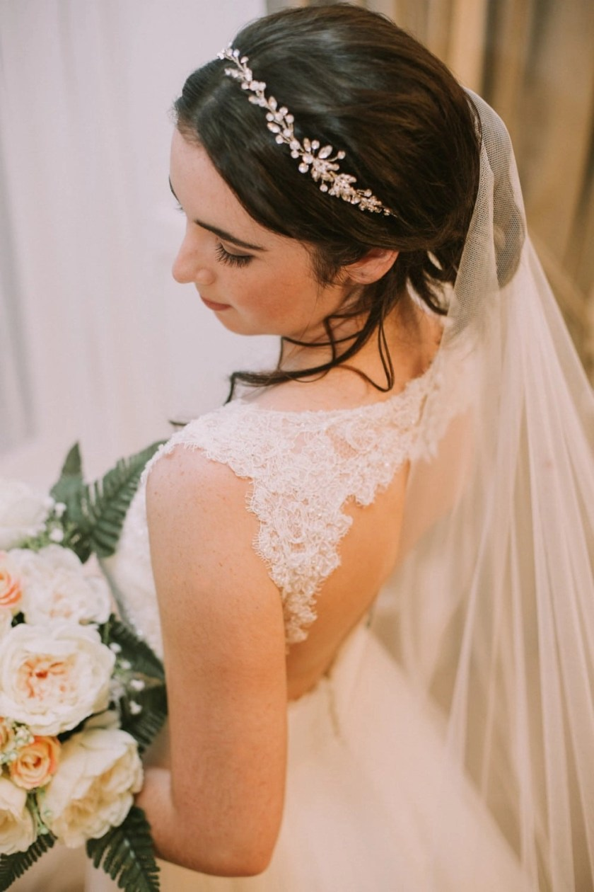 Close up of bride wearing hand cut barely there waterfall cut chapel length veil
