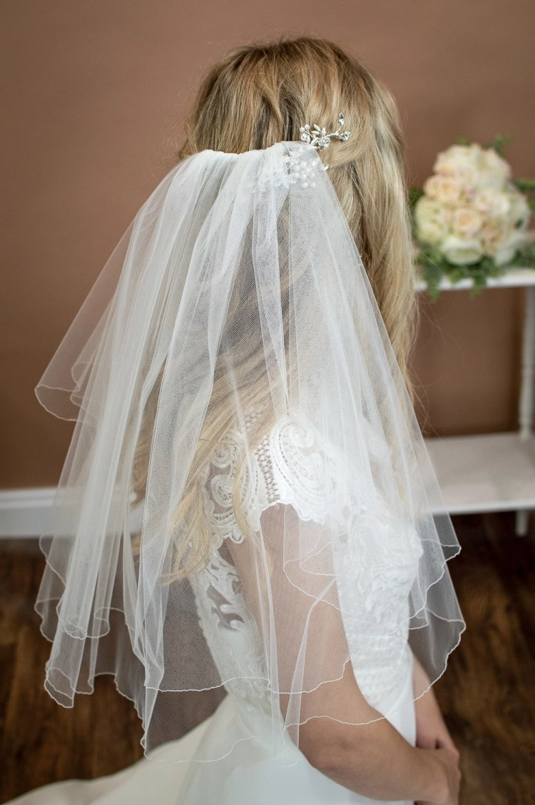 Charlie - two layer shoulder length veil with a pencil edge on a bride closeup