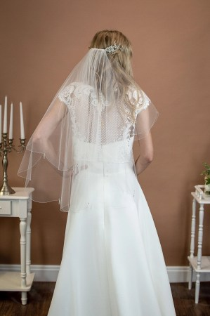 Danika - two layer short waist length wedding veil with a scalloped edge and teardrop crystals on a bride