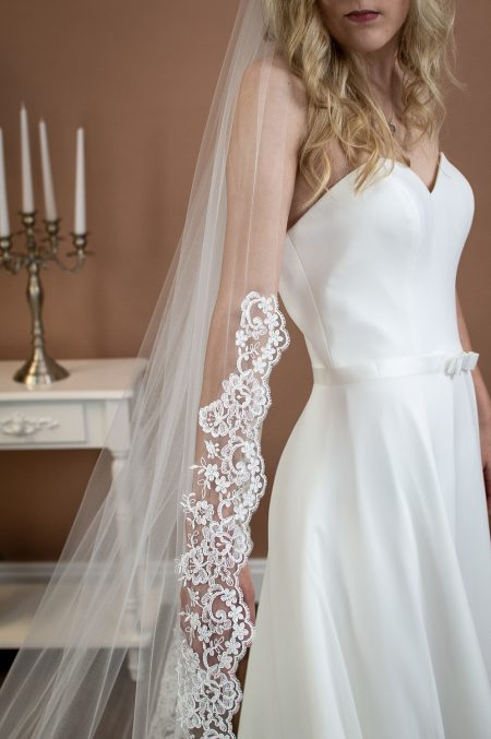 Eleanor - single layer chapel length veil with tapered lace to elbow level closeup on arm