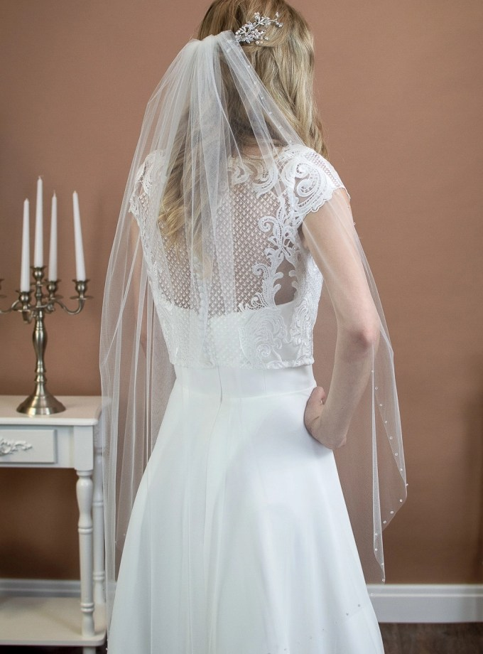 Stella - one layer fingertip length veil with a cut edge and a single row of crystals on a bride