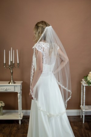 Zoe - short single layer fingertip length veil with a beaded narrow floral lace on a bride