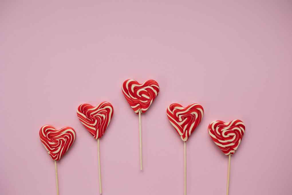 tasty lollipops in form of hearts placed on pink background