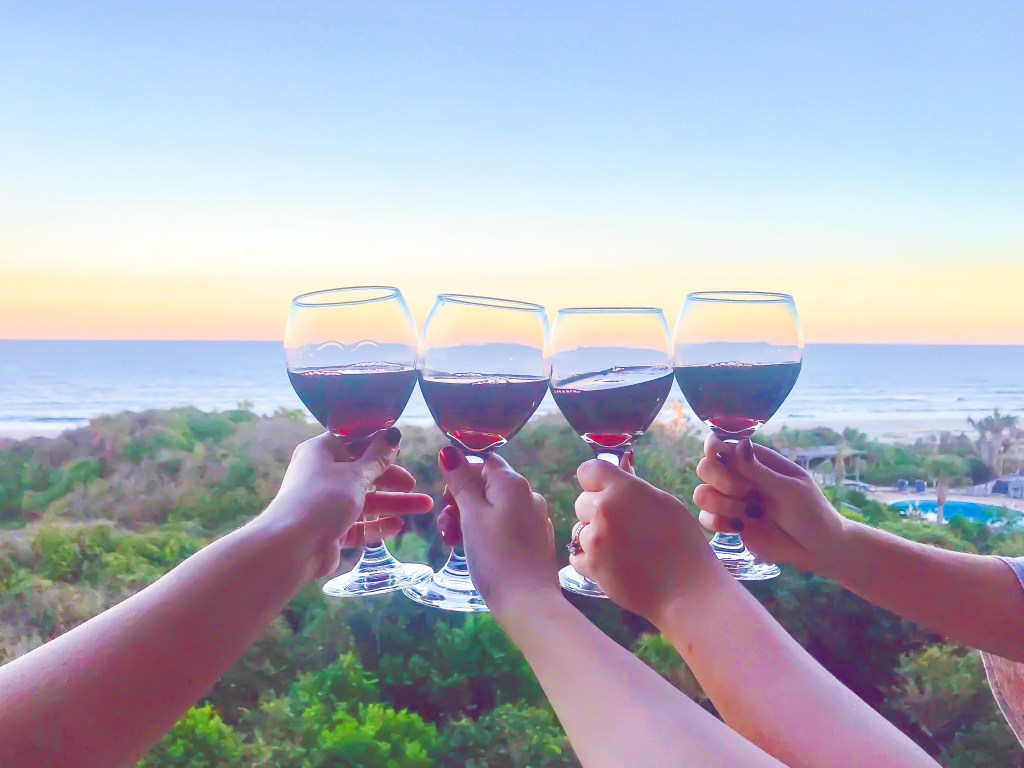 girls getaway in Amelia Island, Florida // wine glasses clinking at sunset