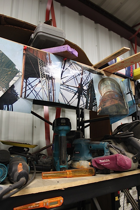 Photos of Sombrero Lighthouse are tacked up on the tool shelf in Larry Herlth's workshop in Islamorada. He said he references these photos to make sure all the details are correct.