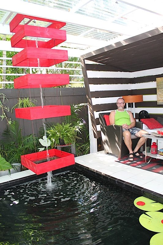Artist Jack Henry Jr. lounges in the backyard next to the 'Stargate' inspired fountain his partner Richard Logan created.