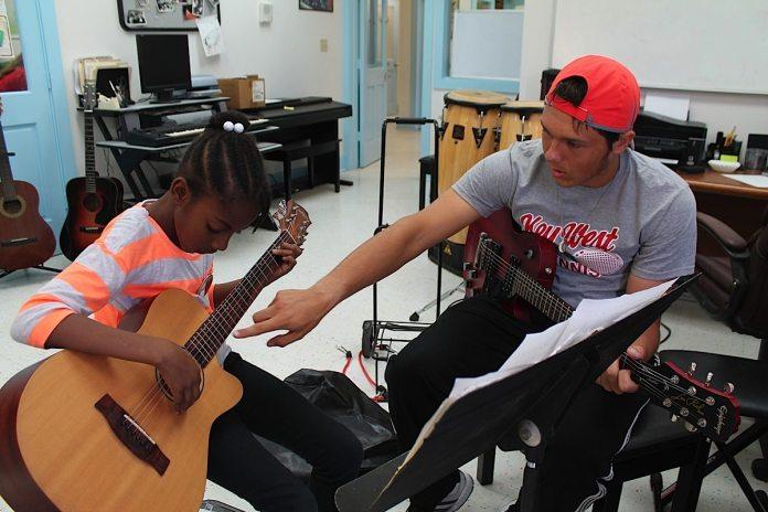Guitar teacher Chris Bujack, 17, helps Melissa Talerand, 9, fret some basic chords on the guitar.
