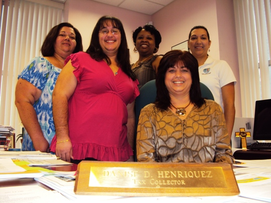 The Honorable Danise Henriquez (sitting) and staff. Pictured from left to right are Angela Hitchcock, assistant tax collector; Jessica Gil, tourist development manager; Sabrina Roberts, deputy clerk; and Mercedes Knowles, delinquent deputy clerk