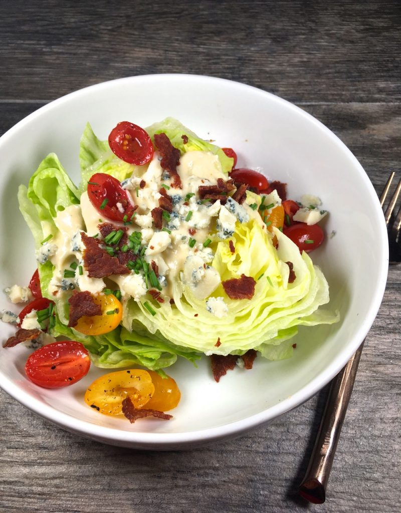 Wedge Salad made with Goat Cheese Blue Cheese & Goat's Milk Yogurt Salad Dressing, Garnished with marinated tomatoes, turkey bacon and chives