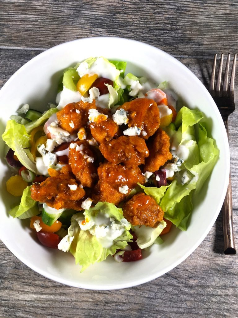 Gluten-Free Fried Chicken Tossed in Buffalo Sauce on a Salad with Goat Milk Blue Cheese Dressing