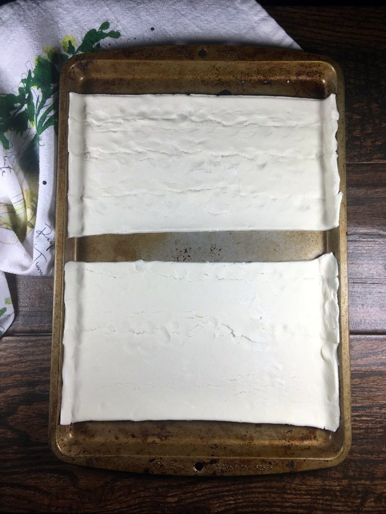Schär gluten-free puff pastry crust cut in half on a baking sheet