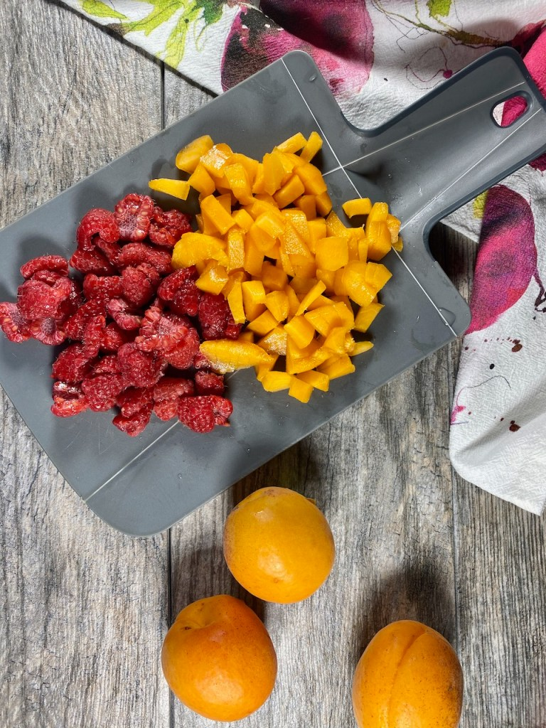 About 5 ounces raspberries cut in half and 2 small apricots cut into small pieces after removing the skin