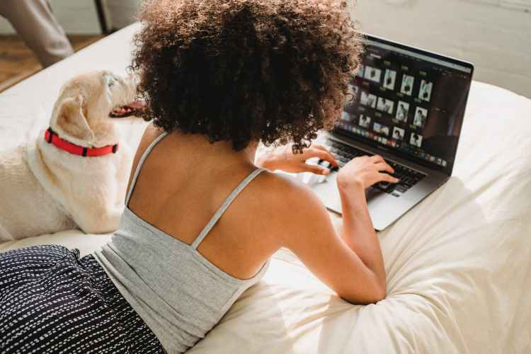 black woman browsing laptop with dog on bed