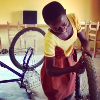 """This is Charity, my new favorite student. When I asked if anyone could tell me how to change a flat she leapt right up and started teaching the other girls. The ladies of Suhum have skillz, but too often their brothers take their bikes and break them. When asked what she wanted to be when she grew up, Charity told me she wanted to be a nurse. """"Not a bike mechanic?"""" I asked. Everyone laughed. Ghanaian schoolchildren know better than to aspire to bike dirtbaggerey as a profession."""