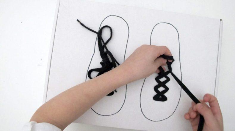 Kind uebt Schuhebinden Montessori Material