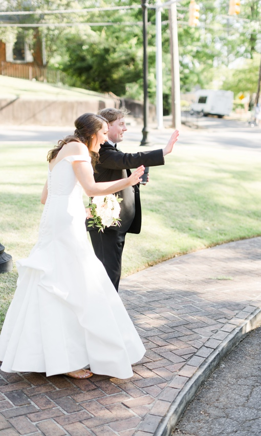 bride and groom waving to guest