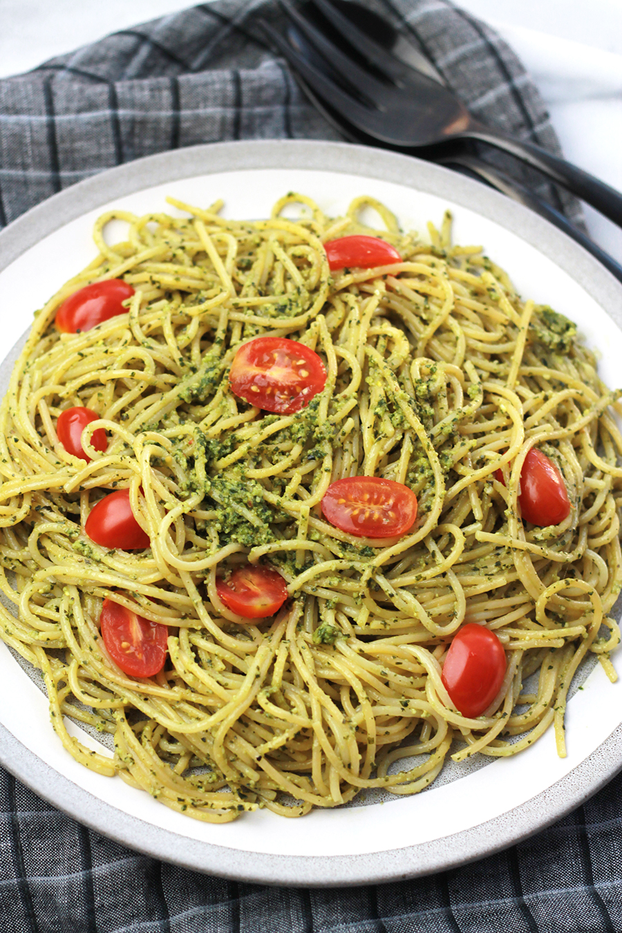Plate of pasta tossed with Vegan Pesto with tomatoes on top.