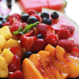 Watermelon, pineapple, peaches, blueberries, strawberries, and raspberries over rubbed kale.