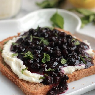 Lightly sweetened creamy lemon ricotta on toast topped with sweet juicy wild blueberry compote, sprinkled with mint. Sumptuosity on a plate.