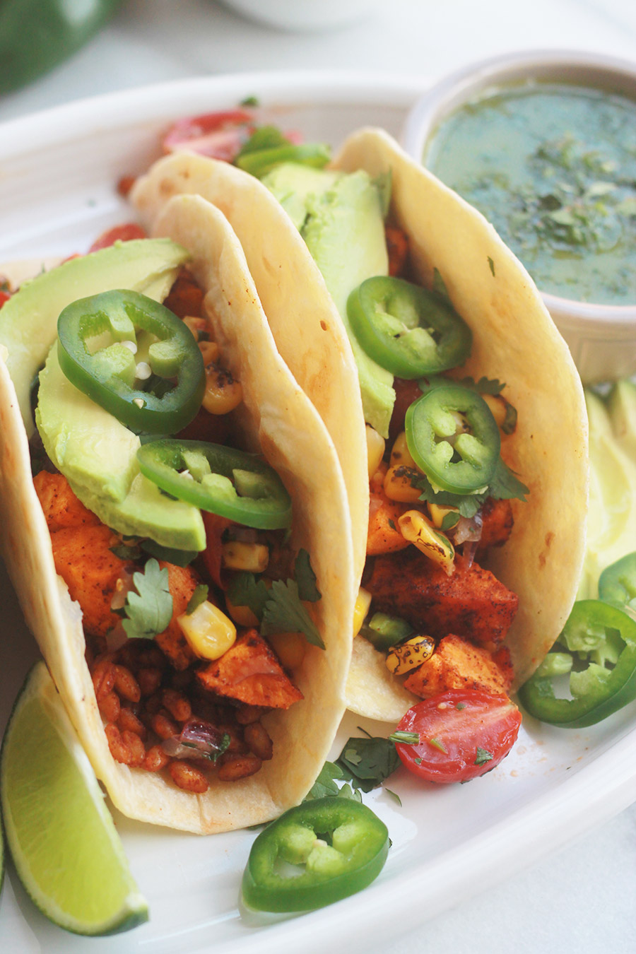 Roasted Sweet Potatoes and Farro Tacos with sliced jalapenos and avocado.