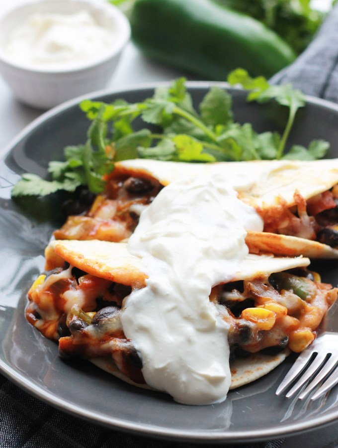 Baked Black Bean Tacos with Red Chile Sauce on plate topped with vegan sour cream
