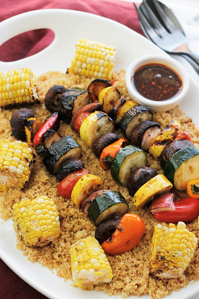 Platter of grilled veggie kabobs, corn over couscous.