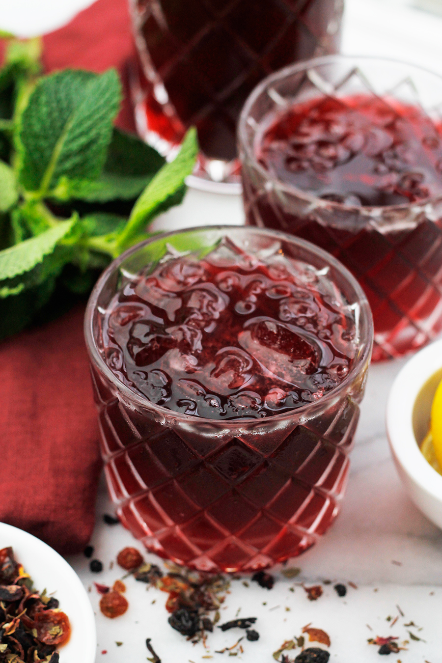 Angled overhead shot of two glasses of Sweet Vermouth Hibiscus Tea Cocktail.