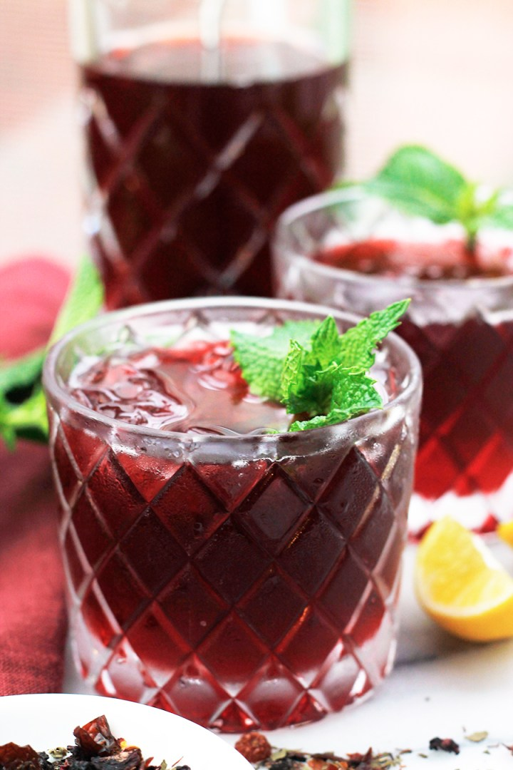 Shot of Sweet Vermouth Hibiscus Tea Cocktail in double old-fashioned glasses garnished with fresh mint.