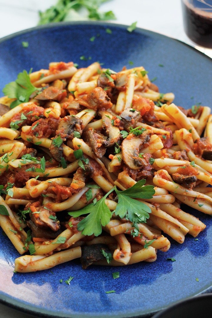 Close-up of blue plate filled with Vegan Eggplant Mushroom Bolognese Sauce tossed with Casarecce pasta.