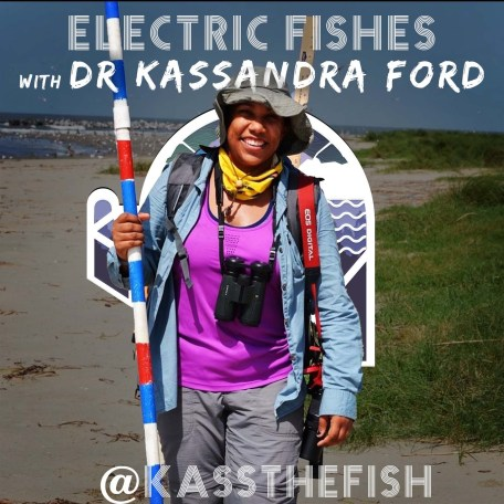 Dr. Kassandra Ford in field clothes (grey field pants, a blue fishing shirt, a purple athletic tank, and a large brimmed hat. She's also wearing binoculars, a camera, and a handkerchief and carrying a yard stick and a long pole for field work. She's smiling and on a beach near green marshland. This picture was taken on a Louisiana barrier island.