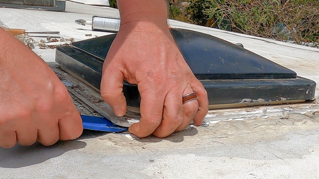 Use a plastic panel removal tool or scraper to pry the old RV roof vent fan from the RV roof.