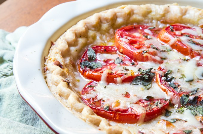 Tomato pie with layers of tomatoes interleaved with cheese, oregano, mayonnaise, salt and pepper.