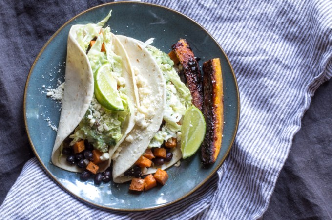 Tacos filled with spicy black beans, roasted sweet potatoes, and cabbage - all topped with a tomatillo-avocado sauce and cheese. Candied plantains are on the side!