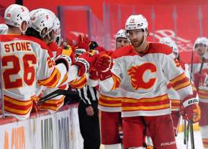 MONTREAL, QC - APRIL 14: Noah Hanifin #55 of the Calgary Flames celebrates with the bench after scoring a goal against the Montreal Canadiens in the NHL game at the Bell Centre on April 14, 2021 in Montreal, Quebec, Canada. (Photo by Francois Lacasse/NHLI via Getty Images)