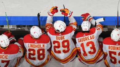 EDMONTON, AB - APRIL 29: Elias Lindholm #28, Dillon Dube #29 and Johnny Gaudreau #13 of the Calgary Flames watch the play from the bench during the game against the Edmonton Oilers on April 29, 2021 at Rogers Place in Edmonton, Alberta, Canada. (Photo by Andy Devlin/NHLI via Getty Images)