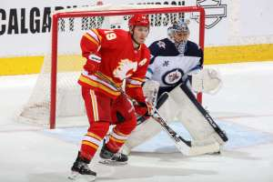 CALGARY, AB - MAY 5: Matthew Tkachuk #19 of the Calgary Flames battles in front of the net against Conor Hellebuyck #37 of the Winnipeg Jets at Scotiabank Saddledome on May 5, 2021 in Calgary, Alberta, Canada. (Photo by Gerry Thomas/NHLI via Getty Images)