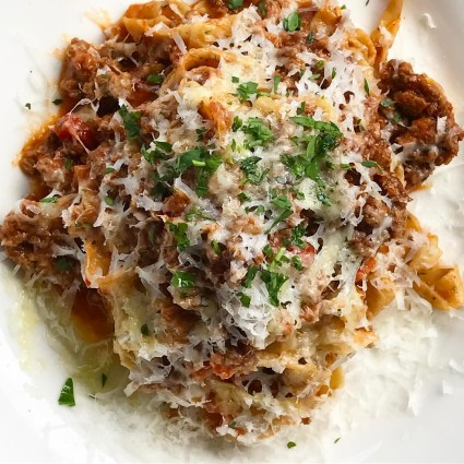 Duck Bolognese with shaved parmesan cheese - Brasswood Bar + Kitchen