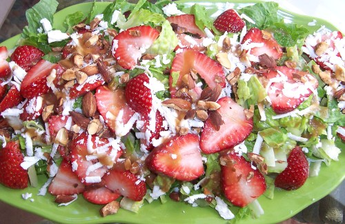 Strawberries and grated feta cheese on a bed of greens