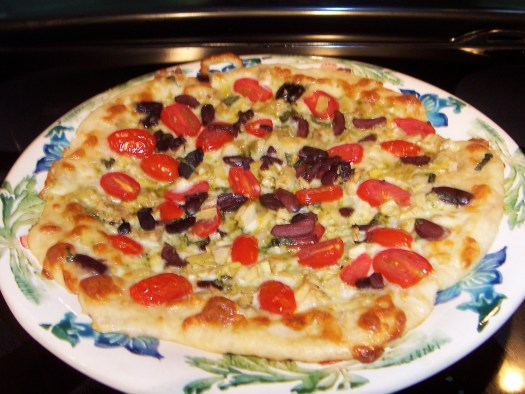 Golden pizza with tomatoes, pesto, black olive on a round platter
